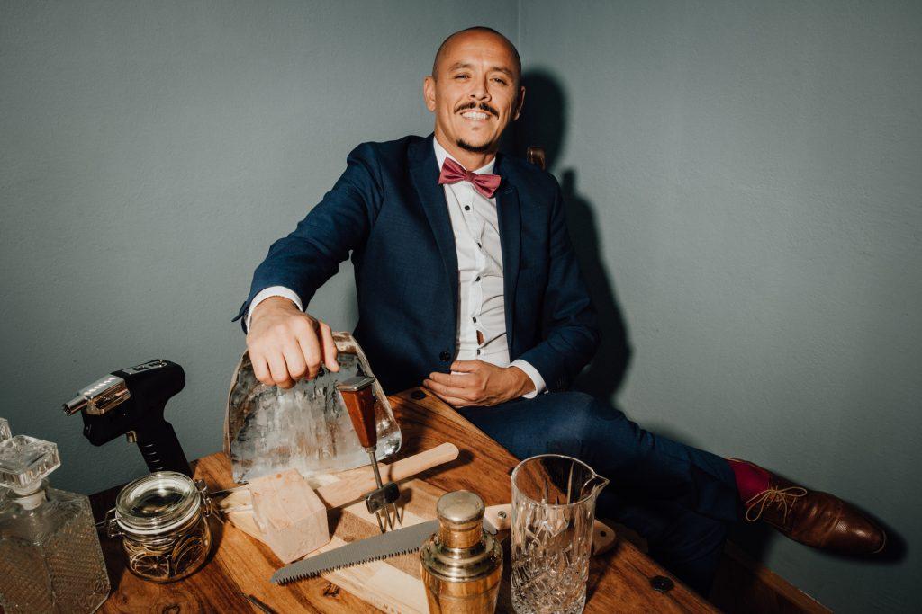 Portrait von Andreas Lugmayr Cocktail Shaker und diversen Bar Utensilien
